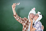Composite image of geeky hipster couple taking selfie with smart phone