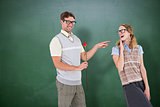 Composite image of geeky hipster holding rose and pointing his girlfriend
