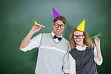Composite image of geeky couple with party hat and party horn