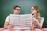 Composite image of geeky hipster couple reading newspaper