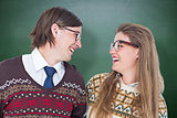 Composite image of happy geeky hipster couple looking at each other