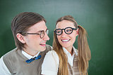 Composite image of geeky hipster couple smiling at each other