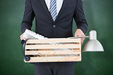 Composite image of businessman holding box of his things