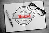 Brand against overhead of open notebook with pen and glasses