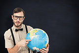 Composite image of geeky hipster holding a globe