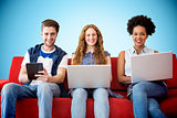 Composite image of young adults using electronic devices on couch