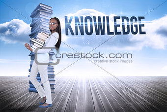 Knowledge against stack of books against sky