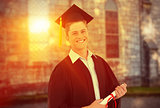 Composite image of a smiling man with a degree in hand as he looks at the camera