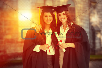 Composite image of two women embracing each other after they graduated from university