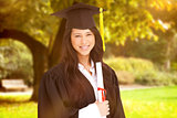 Composite image of a woman standing to the side slightly with her degree and dressed in her graduati