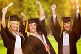 Composite image of three students in graduate robe raising their arms
