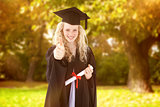 Composite image of teenage girl celebrating graduation with thumbs up