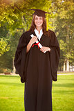 Composite image of full length shot of a graduate holding a degree and looking at the camera