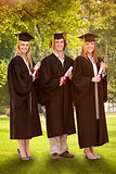 Composite image of three smiling students in graduate robe holding a diploma