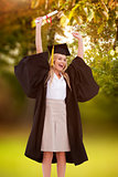 Composite image of blonde student in graduate robe holding up her diploma
