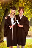 Composite image of two students in graduate robe shoulder to shoulder