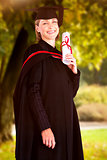 Composite image of confident graduated woman looking at the camera