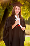 Composite image of a smiling woman with her degree as she looks at the camera