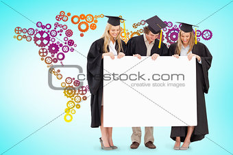 Composite image of three smiling students in graduate robe holding a blank sign