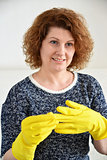 Woman takes off rubber gloves after cleaning