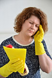 woman with a headache after cleaning the house