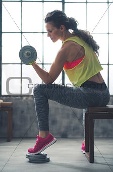 Fitness woman lifting dumbbell in loft gym