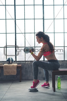 Athlete woman lifting dumbbell in loft gym