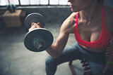 Closeup on fitness woman lifting dumbbell in loft gym