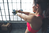Seen from behind fitness woman lifting dumbbell in loft gym