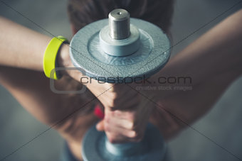 Fitness woman holding dumbbell behind head. Close up