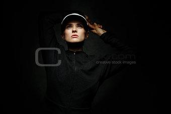 Fit woman in tennis visor looking up against black background