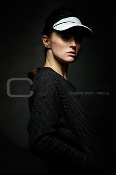 Portrait of young fit woman against black background