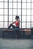 Fitness woman with cell phone sitting in loft gym