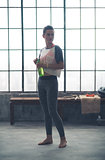 Fitness woman with bottle of water in loft gym