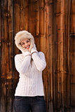 Happy woman in knitted sweater standing near rustic wood wall