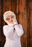 Happy woman fooling around with furry hat near rustic wood wall