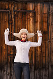 Smiling woman fooling around with furry hat near wood wall