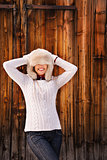 Young woman pulled furry hat over her eyes near rustic wood wall