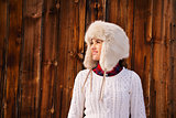 Happy woman in furry hat near rustic wood wall looking aside