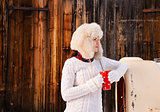 Woman in sweater and furry hat with cup near rustic wood wall