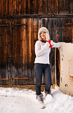 Happy woman in furry hat with red cup near rustic wood wall