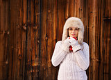 Woman in white knitted sweater with cup near rustic wood wall