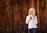 Pensive young woman in furry hat with cup near rustic wood wall