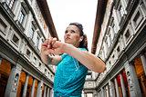 Fitness young woman stretching next to Uffizi gallery, Florence