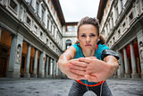 Sportswoman with headset is stretching next to Uffizi gallery