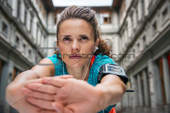 Close up on sporty young woman with earphones stretching