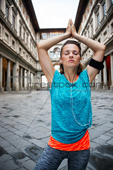 Fitness young woman with earphones doing yoga outdoors. Florence