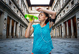 Fitness woman is drinking water while outdoors training
