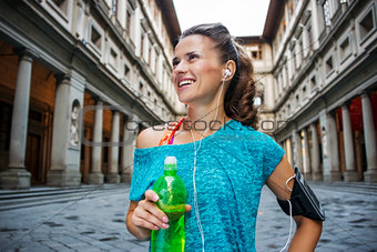 Portrait of happy fitness woman with bottle of water. Florence