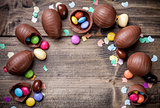 Chocolate easter eggs and sweets on wooden background